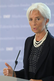 Christine Lagarde accessorized a conservative yet chic outfit with layered pearl necklaces during her delivero of the state of the UK economy.