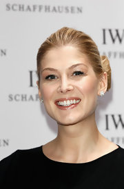 At the 22nd SIHH High Jewelry Fair, Rosamund Pike wore her blond hair pulled back and looped into two sections to resemble a bow.