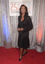 Omarosa Manigault wore a black eyelet blouse with ruffles down the front during the IWMF Courage in Journalism Awards.