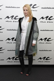 Iggy Azalea visited Music Choice rocking a gray raincoat over a white cutout shirtdress.