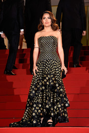 Salma Hayek dazzled at the 'Il Racconto Dei Racconti' premiere in a black and gold Alexander McQueen strapless gown featuring a fitted bodice and a full, tiered skirt.