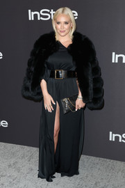 Hilary Duff arrived for the InStyle and Warner Bros. Golden Globes after-party wearing a black fur jacket over a matching high-slit gown.