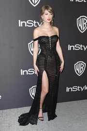 Taylor Swift complemented her dress with black ankle-strap heels by Christian Louboutin.