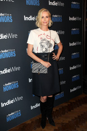 Charlize Theron paired her shirt with a black knee-length skirt, also by Dior.