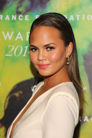 Chrissy Teigen accessorized with a pair of dangling gemstone earrings by Jacob & Co. for a glam finish.