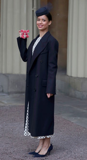 Gugu Mbatha-Raw attended an investiture ceremony at Buckingham Palace wearing a double-breasted navy coat over a polka-dot dress.