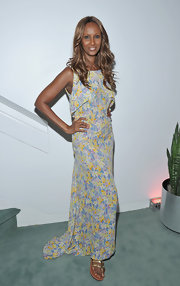 Iman went for a more subdued look at the Invisible Beauty event in a floral floor-length frock and gold gladiator sandals.