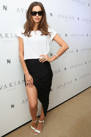 Irina Shayk glammed up her plain top with a sophisticated asymmetrical black skirt.