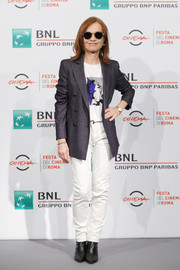 Isabelle Huppert teamed white jeans with a graphic tee for a photocall during the 2018 Rome Film Fest.