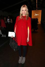 Laura Whitmore attended the Issa London fashion show wearing slouchy gray ankle boots with a red coat.