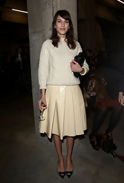Alexa Chung is not stranger to funky fashion. The star paired a cable-knit sweater with a pleated skirt and heels at the J.W. Anderson runway show in London.