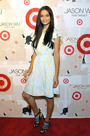 Shanina paired her feminine frock with bright blue strappy sandals.