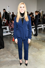 Zosia Mamet attended the Jason Wu fashion show wearing a navy pantsuit with ruched sleeves and ruffle detailing.