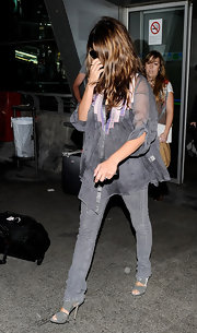 Penelope completed her gray ensemble with wrapped open-toe sandals. The transitional shoe dressed up her casual skinny jeans.