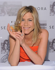 Jennifer Aniston paired her bright orange dress with an elegant diamond cocktail ring.