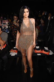 Kylie Jenner channeled her inner Las Vegas showgirl in a fringed gold top by Jeremy Scott while attending the label's fashion show.