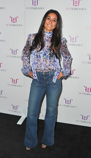 Emmanuelle looked 70's chic in a sheer floral print blouse and high-waisted jeans.