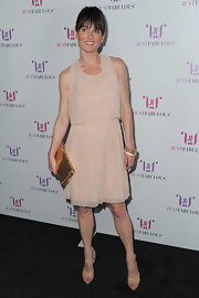 Robin Tunney added shine to her blush chiffon dress with a gold chainmail clutch.