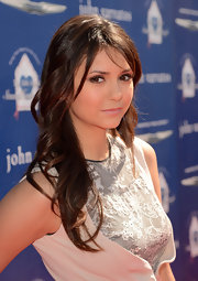 Nina Dobrev showed off her signature chocolate locks with these long curls with side-swept bangs.