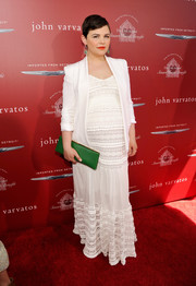 Ginnifer Goodwin accessorized with a green leather clutch for a splash of color to her white outfit.