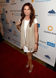 Roma Downey paired a tan vest over her white frock for a slightly casual red carpet look.