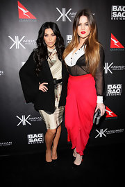 Khloe matched her bright look with a woven black-and-white hard case clutch.