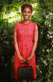 Issa Rae attended the Kate Spade presentation sporting a quilted black purse and pink lace dress combo.