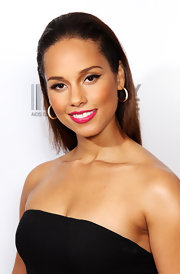 Alicia Keys added a splash of color to her look with bright fuchsia lipstick. Heavy liner on her upper lid completed her flawless look.