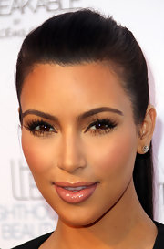 Kim Kardashian wore delicate diamond stud earrings at the fragrance launch for 'Unbreakable.'
