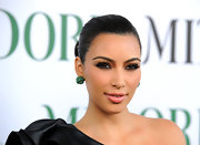 Kim Kardashian paired her sleek bun with emerald green gemstone earrings.