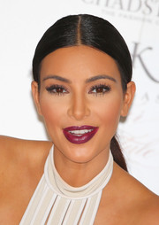 Kim Kardashian pulled her hair back into a sleek center-parted ponytail for a promotional event for her new fragrance.