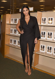 Kim Kardashian looked exotic in a one-sleeve wrap dress with a plunging neckline and a high front slit during her book signing.