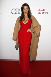 Irina Shayk layered a tan wool coat over her dress for a more season-appropriate look.