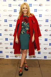 Kylie Minogue wore a bright red wool cape over a sequined floral dress at The World Famous Oxford Street Christmas Lights Switch On Event at the Pandora Flagship Store.