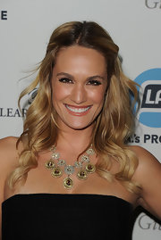 Ashlan Gorse wore her hair half up and half down at L.A.'s Promise 2011 Gala. To recreate her casual look, add a few waves to hair using a large-barreled curling iron. Then, pull back two-inch sections of hair from the front hairline around the temples. Secure the ends behind the ears with bobby pins.