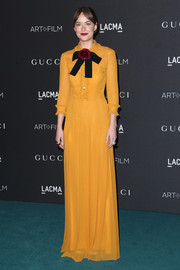 Dakota Johnson brought a dazzling pop of color to the LACMA Art + Film Gala with this floor-length mustard-hued shirtdress by Gucci.
