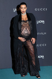 Kim Kardashian topped off her smoldering look with a black lace-panel robe, also by Givenchy.