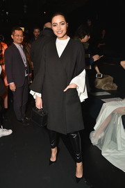 Olivia Culpo layered a black crossover coat over a flowy white blouse for the Lanyu fashion show.