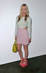 Laura Whitmore sported a color-blocked look during the House of Holland fashion show, consisting of pink wedges, a two-tone dress, and a yellow tote.