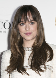 Dakota Johnson sported a sweet wavy 'do with eye-grazing bangs at the Lancome BAFTA nominees party.