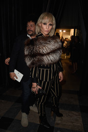 A luxurious fur scarf added a dose of glamour to Noomi Rapace's androgynous outfit at the Lanvin fashion show.