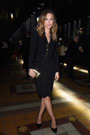 Laura Smet added some glamorous shine to her dress with a metallic gold clutch.