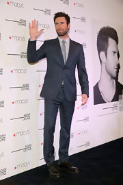 Adam Levine traded in his rocker duds for a class suit at an event for his new fragrance collection.