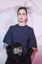 Erin O'Connor attended the 'Le Bal Surrealiste' Dior show carrying a beaded leather purse from the label.