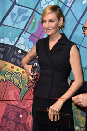 Uma Thurman accessorized with a simple yet chic suede  clutch at the Printemps Christmas decorations inauguration.