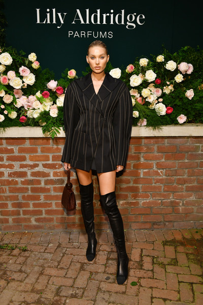 Elsa Hosk accessorized with a brown By Far leather wristlet.
