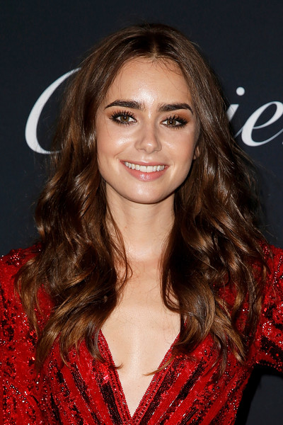 Lily Collins Long Curls [hair,fashion model,beauty,human hair color,hairstyle,eyebrow,chin,long hair,layered hair,brown hair,cartier mansion on september 6,cartier juste un clou new york event,new york city,lily collins]
