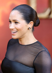 Meghan Markle polished off her look with a pair of diamond studs by Nikos Koulis.