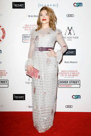 Florence Pugh styled her dress with a pink velvet envelope clutch.