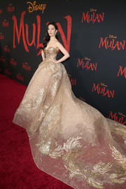 Yifei Liu made a grand entrance in a strapless gold Elie Saab Couture gown with an impossibly long train at the world premiere of 'Mulan.'